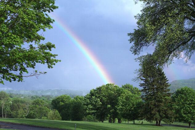 rainbow in a blue sky over a vast green landscape, tended with abundant trees, near Tanglewood, Lenox, MA.